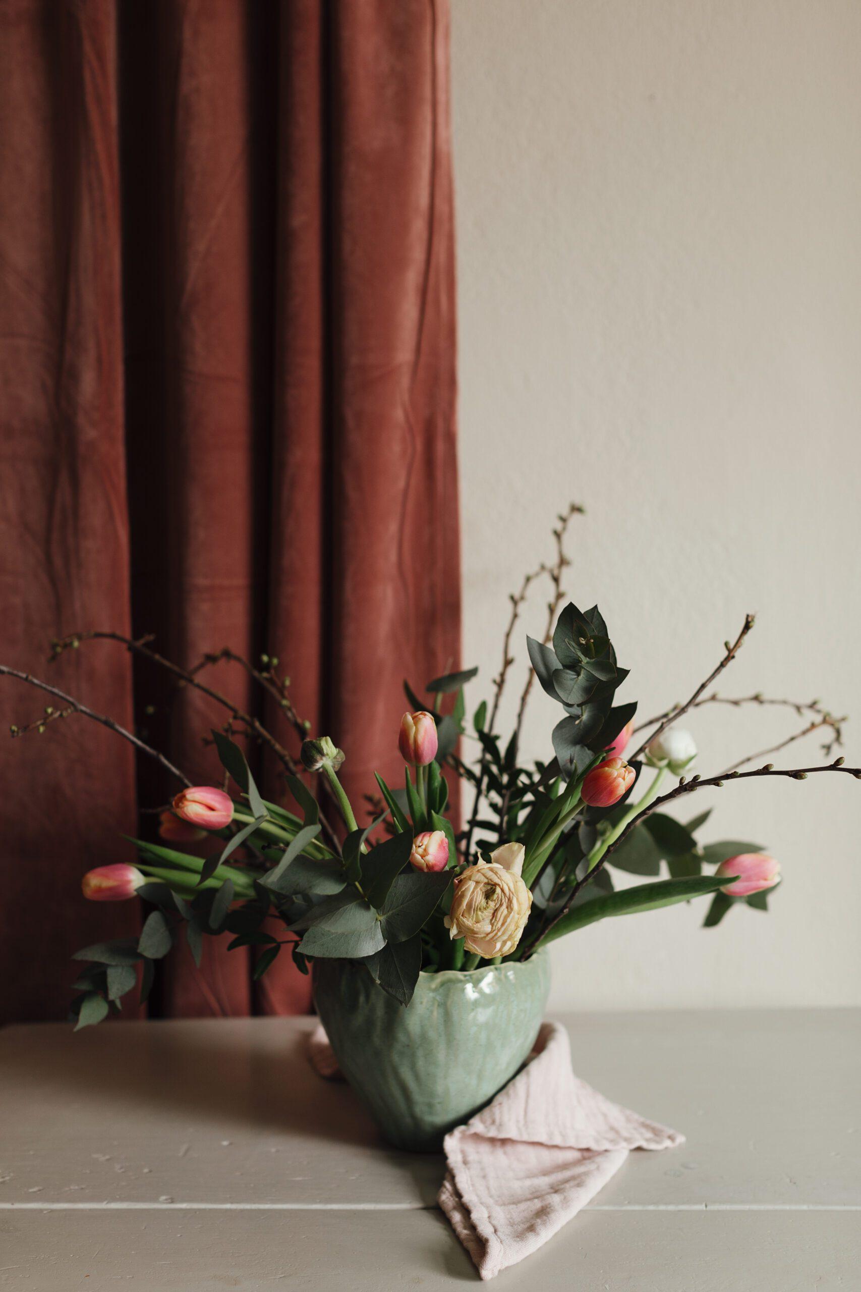gron kruka med blommor och en rosa gardin